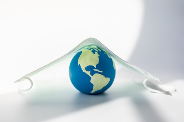 Wereldwijd concept voor gezondheidszorg en bescherming. close-up van miniwereldbal onder chirurgisch gezichtsmasker