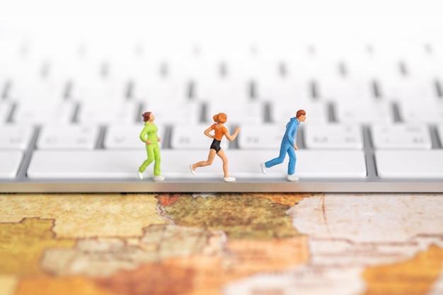 Wereldwijd sport- en technologieconcept. sluit omhoog van groep agent miniatuurcijfers die op computertoetsenbord lopen op wereldkaart.