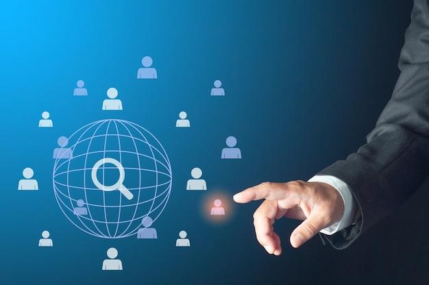 Wereldwijd zakelijk leiderschap zoeken concept. zakenman vinger wijzend virtueel mensensymbool over de hele wereld