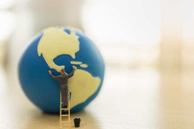 Wereldwijd zorgconcept opslaan. sluit omhoog van arbeiders miniatuurmensen die zich op trede bevinden en miniwereldbal schoonmaken met watertank op houten lijst