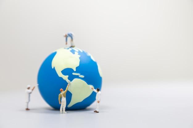 Wereldwijd zorgconcept opslaan. sluit omhoog van groep miniatuurmensen die van de arbeidersschilder en miniwereldbal op witte lijst met exemplaarruimte schilderen schoonmaken.