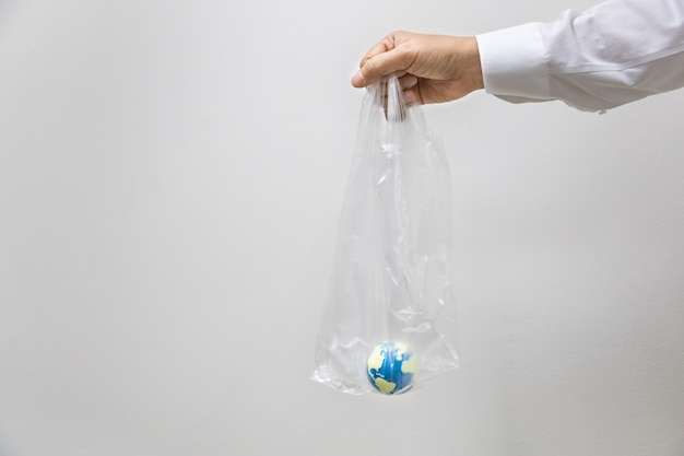 Wereldwijd zorgconcept opslaan. sluit omhoog van zakenmanhand houdend plastic zak met mini binnen wereldbal