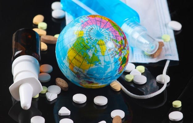 Wereldwijde pandemie covid19. antiseptische fles met blauwe vloeistof, medisch gezichtsmasker, wereldbol, pillen, neusspray op zwart
