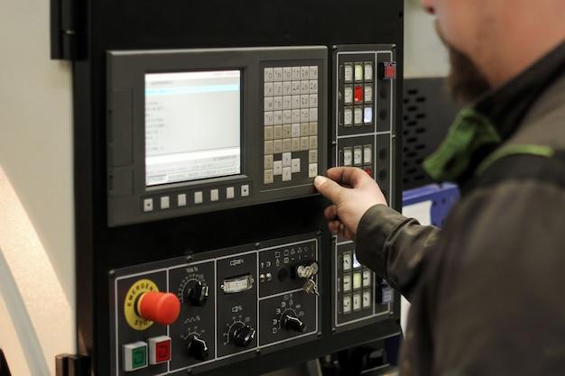 Werk aan het bedieningspaneel van machine cnc. freesmachine voor metaalbewerking. snijden van metaal moderne verwerkingstechnologie.