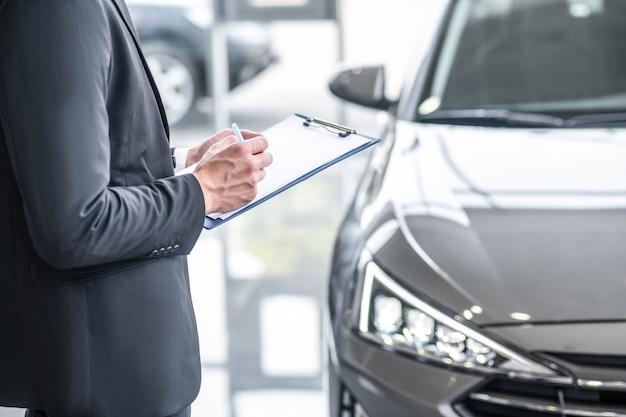 Werk, autodealer. handen van een man in een donker pak die aantekeningen maakt in een document dat in de buurt van de auto in de autosalon staat, zonder gezicht