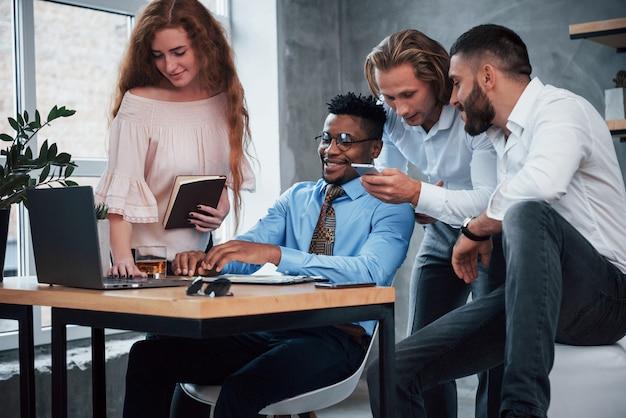 Werk bespreken met behulp van smartphone en laptop. groep multiraciale kantoormedewerkers in formele kleding praten over taken en plannen