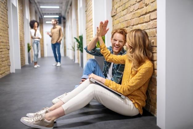 Werk bespreken. twee collega's die op de vloer in de gang zitten en iets bespreken