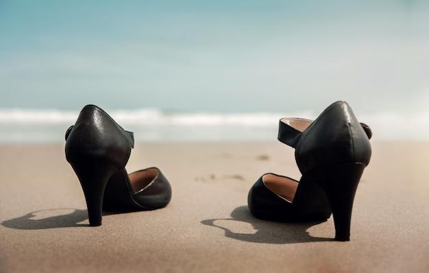 Werk en privé balans concept. zakenvrouw opstijgen werkschoenen op het zandstrand, lopen naar de zee