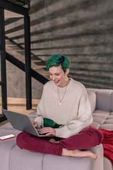 Werk in appartement. succesvolle slimme freelancer met groene ogen die op afstand werkt vanuit haar appartement
