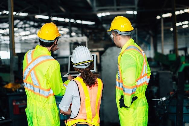 Werk in de fabriek. arbeiders man en ingenieur vrouw team werken samen in veiligheid werkkleding met witte en gele helm met behulp van laptop computer. in de fabriek workshop industrie concept professional