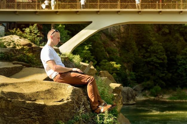 Werk in de natuur concept. man met notebook zittend aan de oever van de rivier in de buurt van de brug over de waterval en groene bomen.