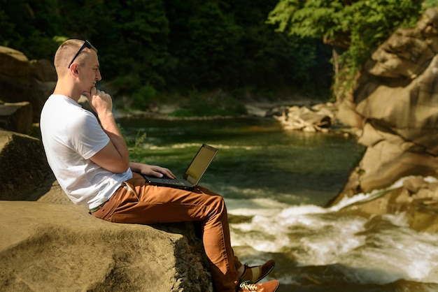 Werk in de natuur concept. nadenkend man met laptop zittend aan de oever van de rivier over de waterval. zijaanzicht