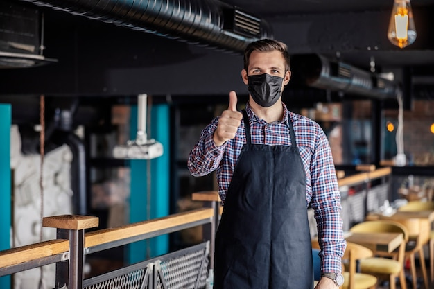 Werk in een restaurant tijdens de covid 19. een portret van een mannelijke ober die een masker met één hand draagt, toont een duim omhoog. goedkeuring voor verantwoordelijk gedrag, sociale afstand