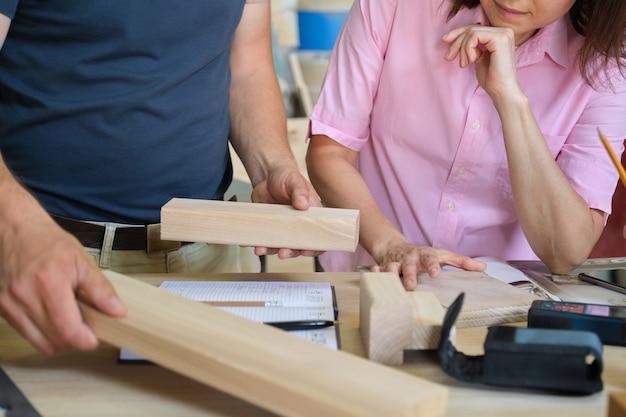 Werk in meubelmakerij timmerwerk, handen van werknemers met houtmonsters close-up
