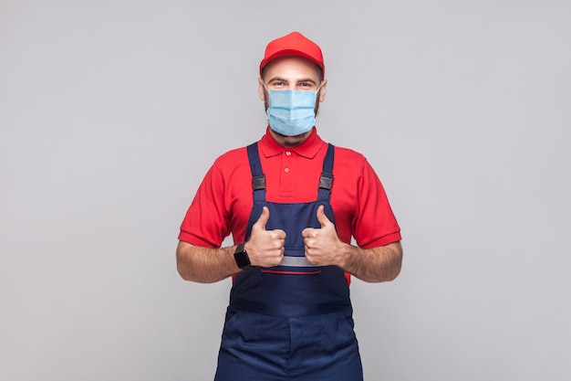 Werk is gedaan! portret van een jonge man met een chirurgisch medisch masker in blauwe overall, rood t-shirt, pet, staand en bonzende tonend en kijkend naar de camera. grijze achtergrond, indoor studio shot geïsoleerd.