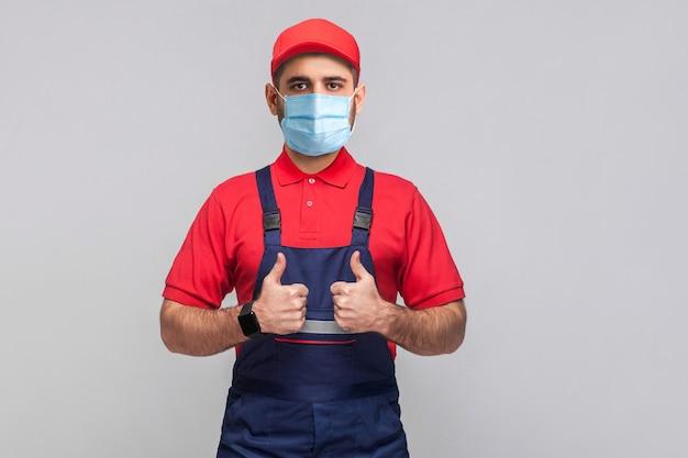Werk is gedaan! portret van een jonge man met een chirurgisch medisch masker in een blauwe overall, een rood t-shirt, een pet, staand en bonzende tonend en kijkend naar de camera. grijze achtergrond, indoor studio shot geïsoleerd.