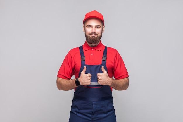 Werk is gedaan! portret van een jonge tevreden vrolijke reparateur met baard in blauwe overall, rood t-shirt en pet, staand en met een glimlach opdagen. grijze achtergrond, indoor studio shot geïsoleerd.