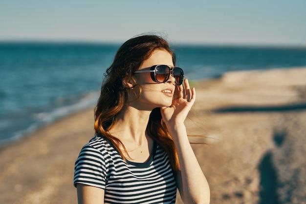 Werk, je zult een vrouwent-shirt in een zonnebril op de frisse luchtvakantie van het strand portretteren