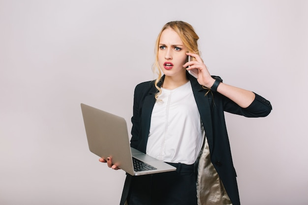 Werk kantoortijd van drukke jonge vrouw in formele kleding met laptop praten over de telefoon. boos humeur, verbaasd, werkend, beroep, secretaresse, kantoormedewerker
