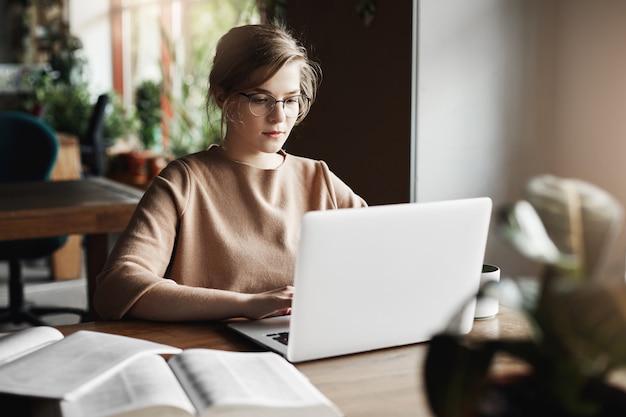 Werk, levensstijl en bedrijfsconcept. knap gericht europese vrouw in trendy bril zitten in café in de buurt van laptop, bezig met laptop, omringd met boeken, notities maken.