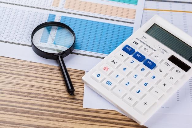 Werk met een vergrootglas, een rekenmachine en papieren