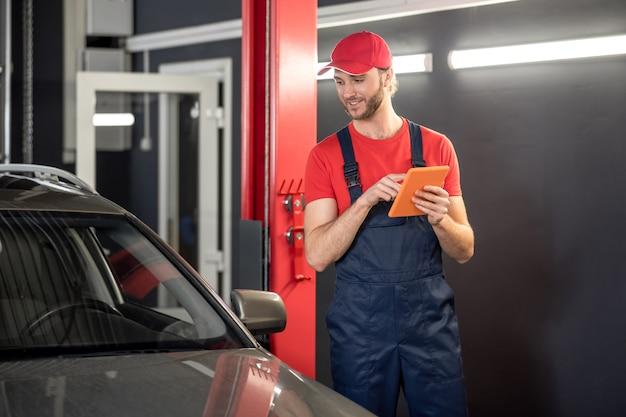 Werk moment. jonge, bebaarde gerichte man in werkkleding met tablet staande in de buurt van auto op zoek vergelijken in werkplaats
