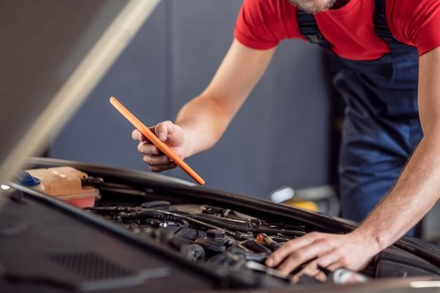 Werk moment. mannelijke handen van monteur in blauwe overall met tablet onder open motorkap van auto