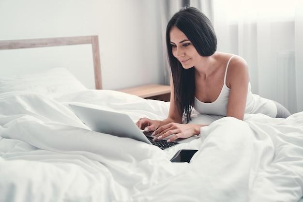 Werk op afstand. mooie langharige vrouw die op haar bed leunt terwijl ze met de computer werkt