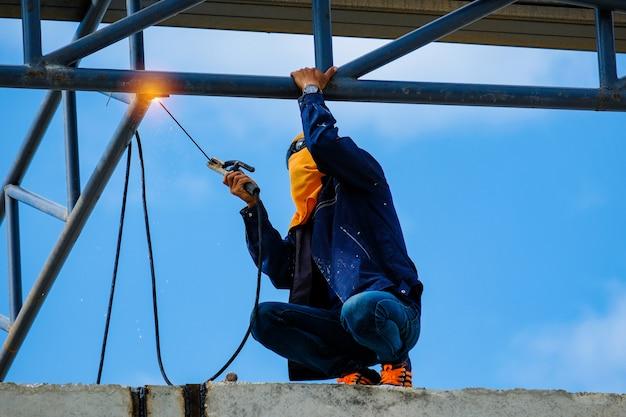 Werk op hoogte, man lasconstructie van fabrieksdak op bouwplaats, hoog risicoberoep.