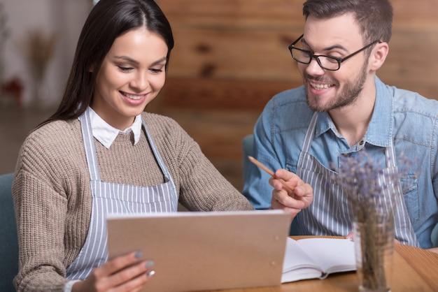 Werk plannen. blij glimlachend paar dat aantekeningen maakt en tablet gebruikt terwijl aan tafel zit.