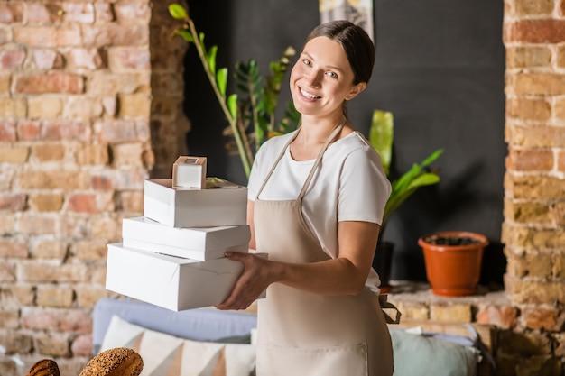 Werk, plezier. jonge volwassen glimlachende vrouw met lang donker haar in schort met dozen voor klaar gebakken goederen in bakkerij