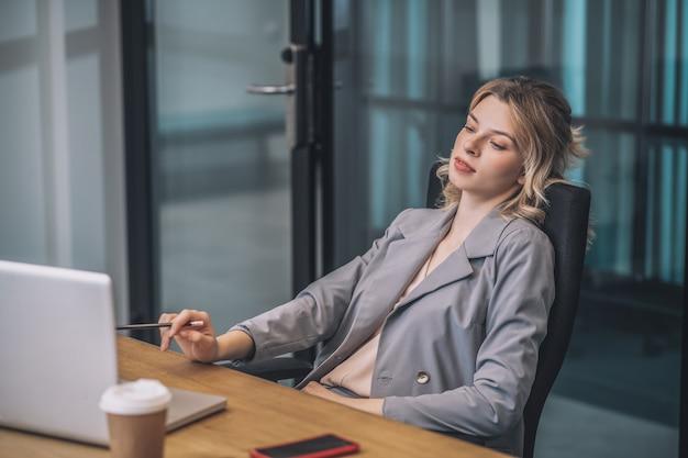 Werk, resultaat. vrij jonge blonde vrouw die in pak met potlood in hand laptop bekijkt die terug als voorzitter leunt