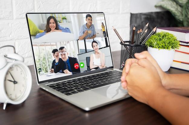 Werk thuis en sociaal afstandsconcept, man praat met collega's over plan in videoconferentie in huis, ontmoet en plant online als covid 19 of corona-virusziekte