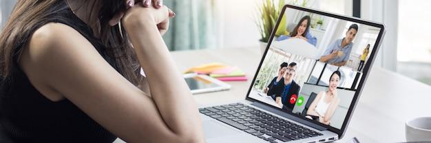 Werk thuis en sociaal afstandsconcept, vrouw die met haar collega's over plan in videoconferentie binnenshuis spreekt, online vergadert en plant als covid 19 of coronavirusziekte