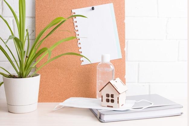 Werk thuis in quarantaine met gezichtsmasker en geldesinfecterend middel, kopieerruimte, potplant, kurkbord en notitieblok op tafel