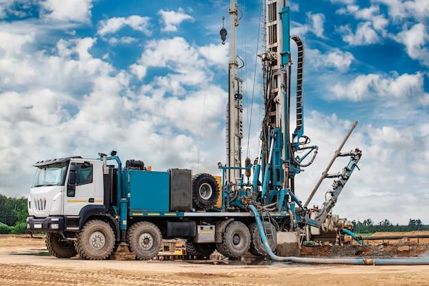 Werk van een booreiland op een bouwplaats tegen een achtergrond van blauwe hemel. verkenning van nuttige mineralen. industrie en bouw.