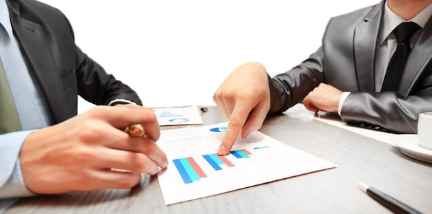 Werk van twee jonge zakenlieden die touchpad gebruiken tijdens vergadering