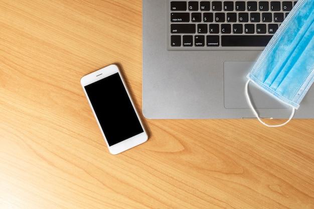 Werk vanuit huis concept. bovenaanzicht laptop, smartphone en gezichtsmasker op houten tafel.