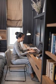 Werk vanuit huis concept een jong meisje met een knot haar doet haar werk op afstand in haar slaapkamer.