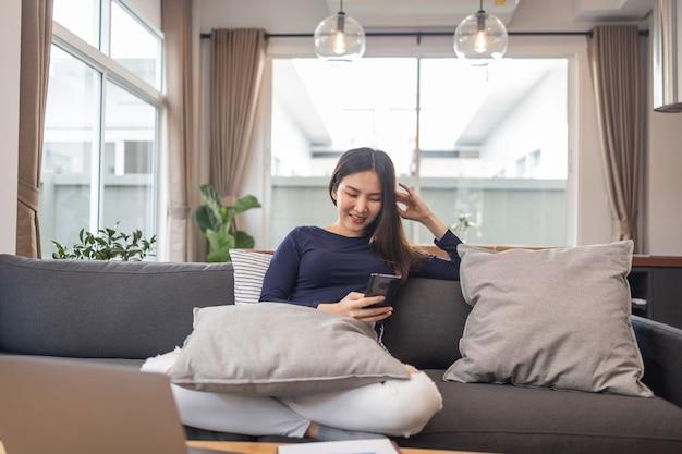 Werk vanuit huis concept een jonge zakenvrouw zittend op een gezellige bank met haar mobiele telefoon chatten met de klanten.