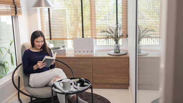 Werk vanuit huis concept een mooie vrouw zittend op een moderne stoel in een goed ingerichte minimale kamer