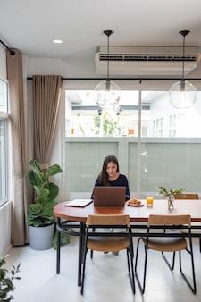 Werk vanuit huis concept een vrouwelijke freelancer die er gelukkig uitziet terwijl ze online werkt in haar eigen ruimte tijdens de covid 19-pandemie.