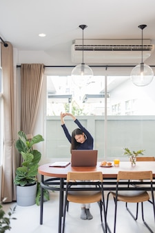 Werk vanuit huis concept een vrouwelijke ondernemer die ontspannen haar armen strekt terwijl ze op afstand in haar huis werkt.
