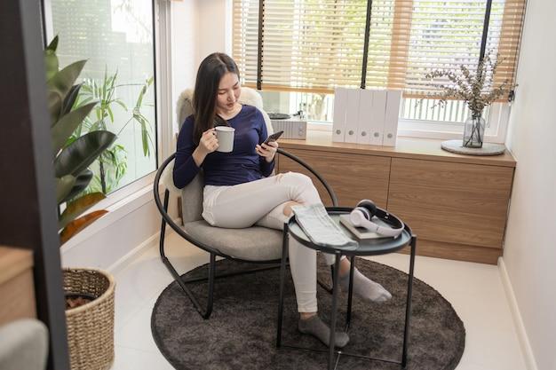 Werk vanuit huis concept een zelfverzekerde vrouw zittend op een moderne stoel houdt een kopje koffie vast en nog een