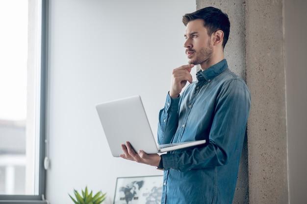 Werk vanuit huis. donkerharige man die bij het raam staat en op een laptop werkt