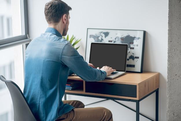 Werk vanuit huis. donkerharige man zit aan de tafel en werkt op een laptop