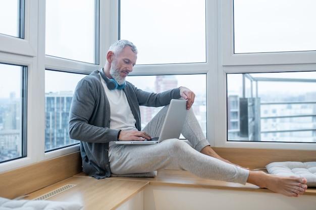 Werk vanuit huis. een volwassen man met een laptop die thuis werkt en er betrokken uitziet