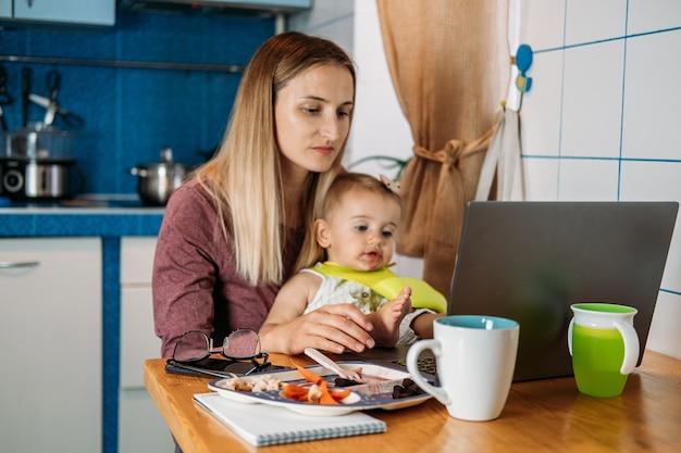 Werk vanuit huis jonge moeder met babymeisje die thuis werkt met behulp van laptop op keukenachtergrond young