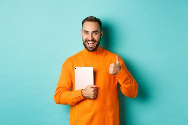 Werk vanuit huis, technologieconcept. knappe man met laptop, duim opdagen, goedkeuren en iets leuk vinden, staande over een turkooizen achtergrond
