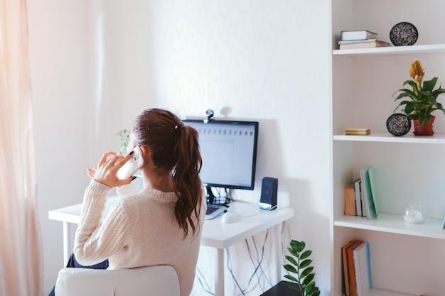 Werk vanuit huis tijdens de pandemie van het coromavirus. vrouw blijft thuis. werkruimte van freelancer. kantoor interieur met computer